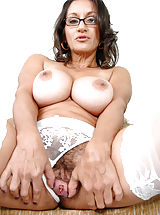 Naked Anilos milf shows off her big tits while busy stroking her hairy pussy with a toy