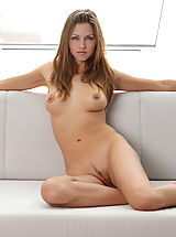Eufrat eagerly slips out of her clothes and stretches her long lithe naked body on a white sofa.